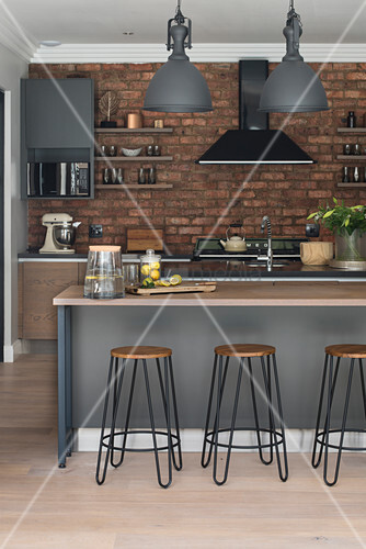 Industrial-style kitchen with exposed brick wall
