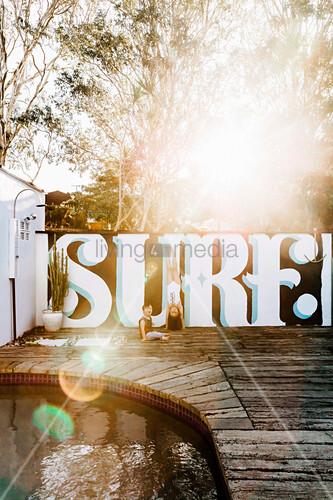 Sonne strahlt über eine Terrasse mit bemalter Mauer und Pool