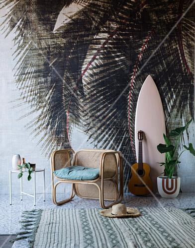 Rattansessel und Surfbrett vor einer Wand mit Palmenmotiv