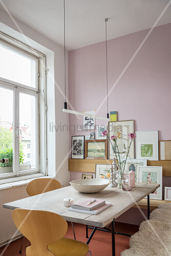 Hängeleuchte über Esstisch mit Holzplatte, im Hintergrund Bildergalerie an rosa Wand