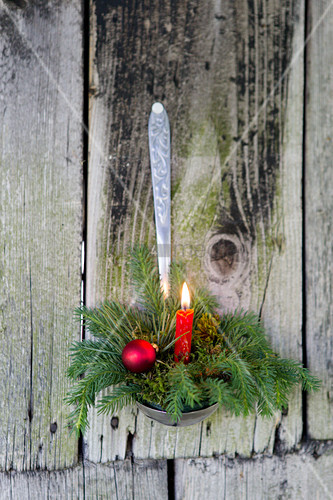 Festive arrangement with candle in ladle