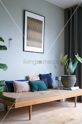 Samtkissen in Blautönen auf einem 50er-Jahre Tagesbett