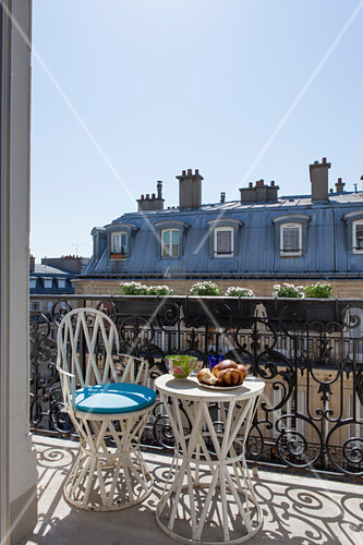 Table and chair on sunny balcony in Paris