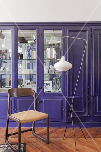 Vintage-Stuhl und Stehleuchte vor einem violetten Einbauschrank