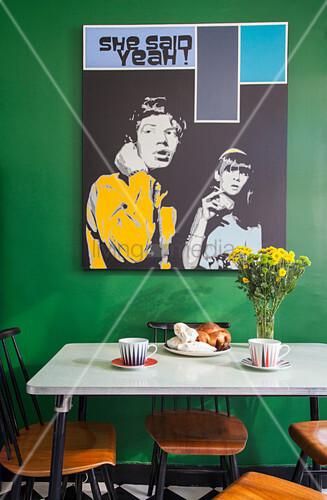 Pop-Art-Bild an grüner Wand über dem Esstisch