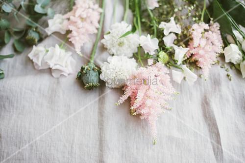 Zarte Blüten in Rosa und Weiß und Mohnkapseln