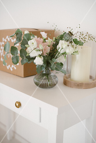Glass vase of eucalyptus branches and white and pink flowers