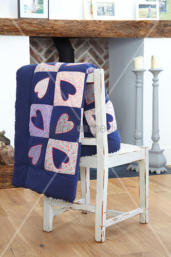 Heart-patterned quilt hung over chair backrest