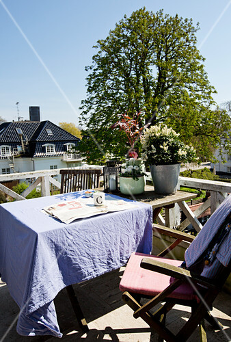 Lilac tablecloth on table and chairs on balcony