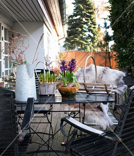 Gartentisch mit Frühlingsblumen auf Terrasse