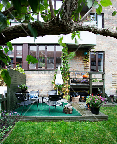 Green rug and seating on wooden deck in garden