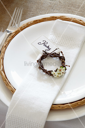 Place setting with white linen napkin and wicker wreath decorated with spring flowers