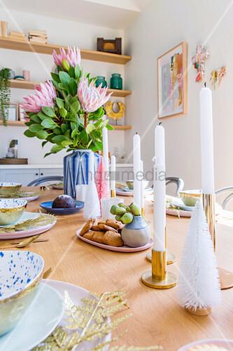 Kerzen und Blumen als Centerpiece auf gedecktem Tisch