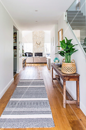 Flur zum offenen Wohnzimmer mit langem Teppich und altem Holztisch