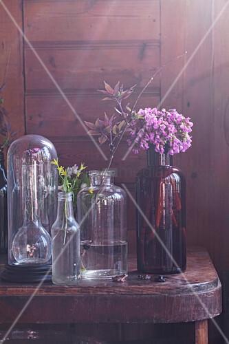Glashaube und Glasflaschen mit Blumen