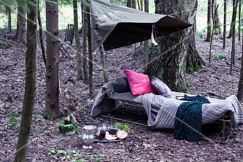 Vintage Feldbett mit Kissen und Decken im Wald
