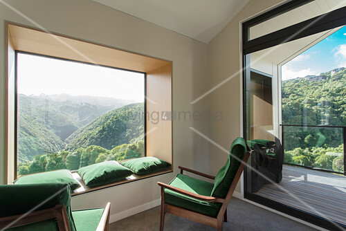 Green armchairs and matching cushions on window seat in panoramic window with view of hilly landscape