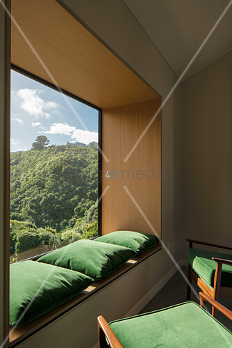 Green armchairs and matching cushions on window sill in panoramic window with view of landscape