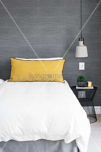 Yellow pillow on bed against grey wall