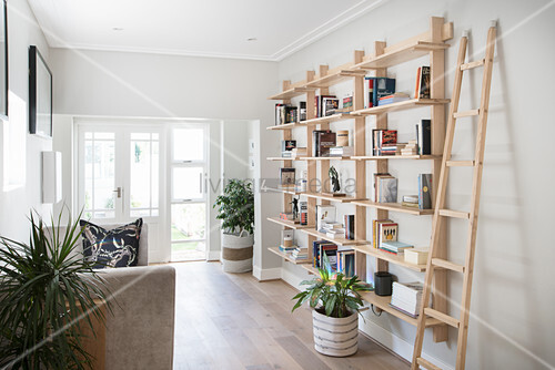 Ladder next to pale wooden shelves on grey wall in hallway