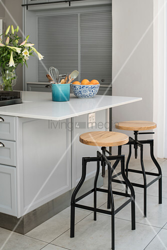 Vase of lilies, kitchen utensils and fruit bowl on island counter with barstools
