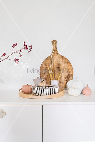 Kürbisdekoration und Holzbrett auf weißem Unterschrank