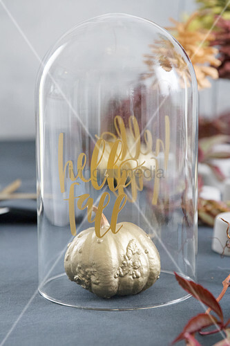 Gold-painted pumpkin under glass cover with autumn greeting