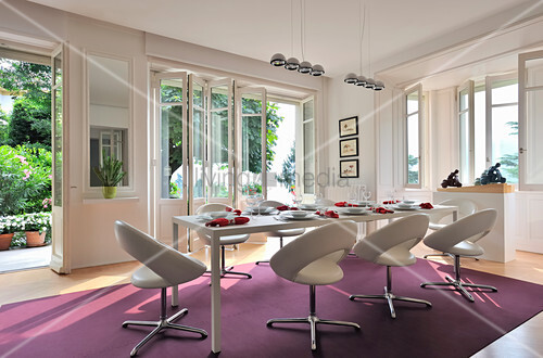 White upholstered chairs around table in modern dining room