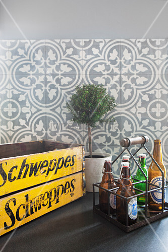 Old drinks crate and bottle carrier in front of patterned tiles