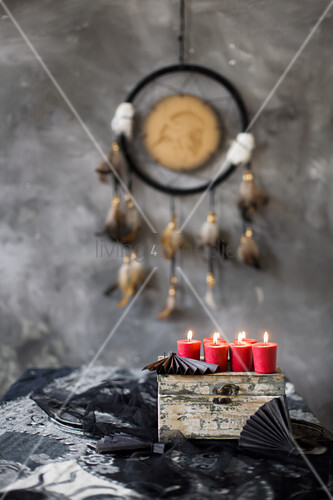 Red candles on top of old wooden box and mystical, ethnic accessories in grey