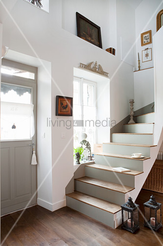 Treppe mit grauen Stufen neben der Haustür eines Landhauses