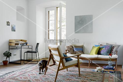 Wohnzimmer mit Schreibtisch und skandinavischen Sitzmöbeln