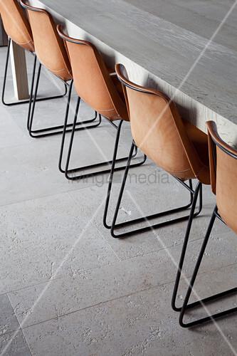 braune st hle mit metallgestell am langen esstisch auf natursteinboden bild kaufen living4media. Black Bedroom Furniture Sets. Home Design Ideas