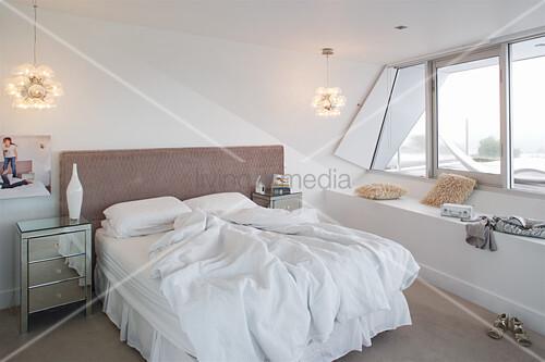 Schlafzimmer in Weiß mit Sitzbank vor dem Fensterband