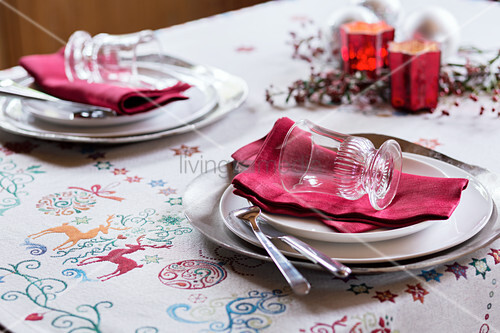 Place settings with red napkins on festive tablecloth