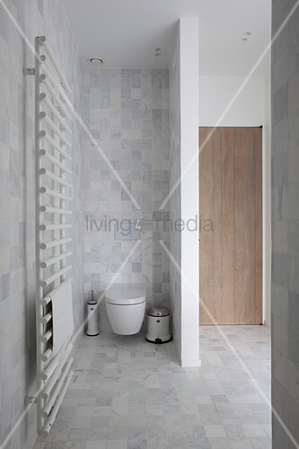 Heated towel rail and toilet behind partition in bathroom