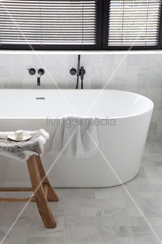 frei stehende badewanne vor fenster und holzhocker bild. Black Bedroom Furniture Sets. Home Design Ideas