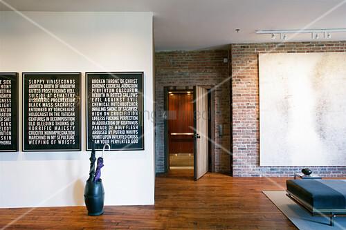 Drei Bilder mit Schriftkunst im modernen Loft mit Backsteinwänden