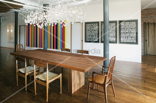 Modern dining table and various chairs in loft apartment with wooden floor