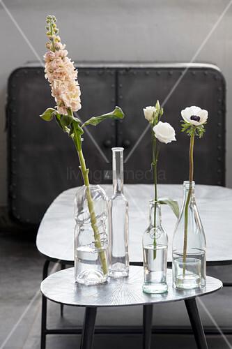 Verschiedene klare Glasflaschen als Blumenvasen auf einem Beistelltisch
