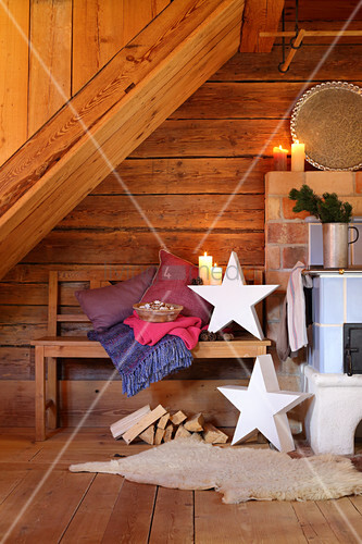 Arrangement of candles and stars in rustic wooden cabin with bench next to log burner