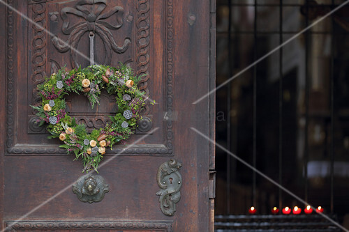 Heart-shaped wreath of heather and conifer twigs on church door