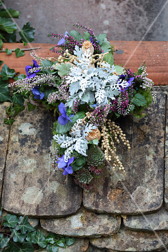 Cross planted with silver ragweed, heather and violas decorating grave