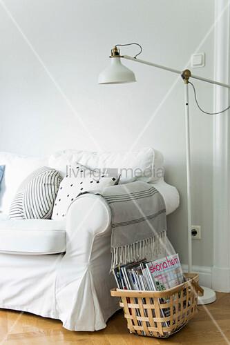 Korb mit Zeitschriften und Stehleuchte neben dem Sofa