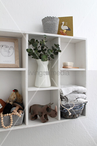 Vase of leaves, toy figurines and basket of folded cloths on white shelves