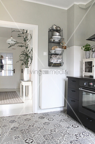 Cement floor tiles in kitchen with wire shelving above radiator