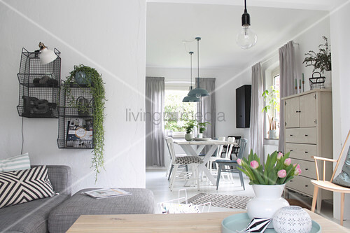 Grey sofa and wire shelving in bright living room with dining area in background