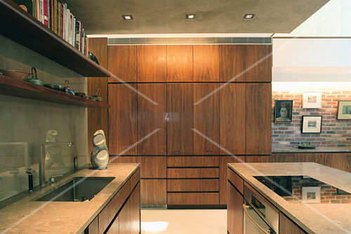 Modern fitted kitchen in dark wood and concrete