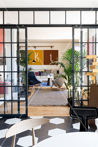 View into living room with designer armchairs through open glass sliding doors