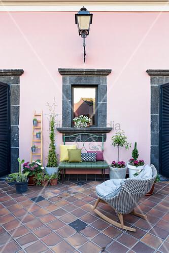 Schaukelstuhl, Grünpflanzen, Bank und verspiegeltes Fenster mit Rahmen aus Lavastein an rosa Wand im Innenhof